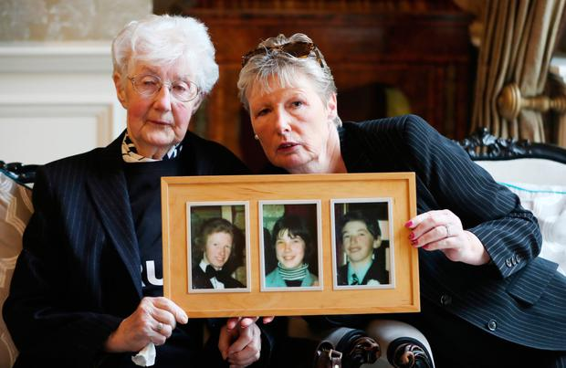 Bridget McDermott and her daughter June hold pictures of relatives William, Marcella and George, who died in the fire