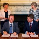 Then Prime Minister Theresa May stands with DUP leader Arlene Foster as DUP MP Sir Jeffrey Donaldson signs the paperwork for the confidence and supply agreement in June 2017