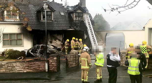 Police and firefighters at scene of the car and house fire in Kilrea yesterday