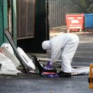 Forensic officers at work following the blaze on Kennedy Way