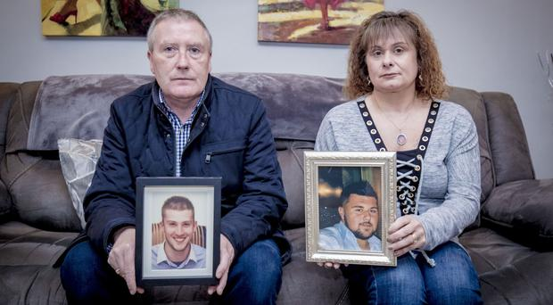 Michael McAnallen and Angela Patterson with photographs of their sons