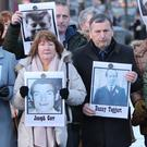 Family members outside Belfast Coroner's Court hold images of some of those who were killed in disputed circumstances in Ballymurphy in August 1971 (Niall Carson/PA)