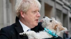 PM Boris Johnson holds his dog, Dilyn, after casting his vote