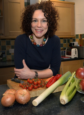 Jane in the kitchen with some fresh fruit and veg