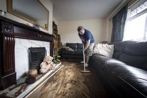 Larchfield Park resident Stephen McCartney attempts to clean his ruined home