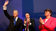 Peter Robinson waves goodbye to the party faithful watched by Nigel Dodds and Arlene Foster after his final leader's speech during the DUP annual conference at La Mon Hotel on November 21, 2015