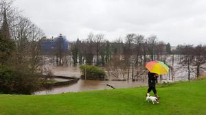 A dog walker near the River Tay in the centre of Perth, as more rain is forecast