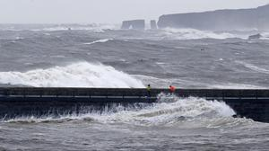 Fishermen brave the rough seas on the South Shields Pier, near Newcastle upon Tyne