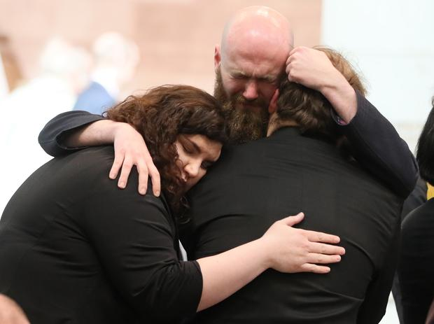 Mourners embrace ahead of the funeral at St Anne's (Brian Lawless/PA)