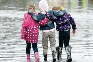 Three young girls take a stroll through the floods in Newcastle