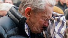 A Holocaust survivor weeps at Auschwitz