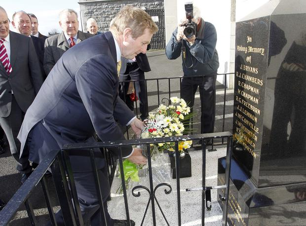 Taoiseach Enda Kenny lays flowers at a memorial to the Kingsmills massacre victims yesterday