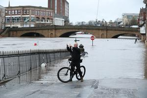 A man on a bicycle taking a photograph in front of floodwaters in York (Danny Lawson/PA)