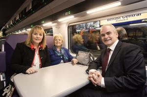 Chris Conway, group chief executive for Translink, and Regional Development Minister Michelle McIlveen with customer Edna Murray, from Belfast, on a newly refurbished Enterprise train leaving Belfast