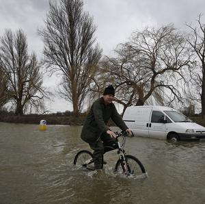A local resident cycles through the flooded part of the town of Staines
