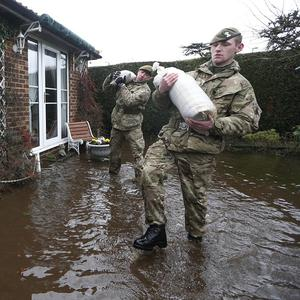 British Army soldiers carry sandbags at the entrance to a flooded house at Chertsey