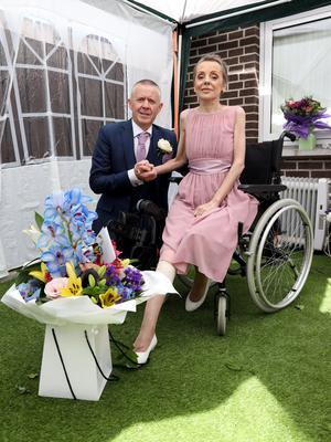 The couple with a bouquet from the Belfast Telegraph