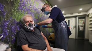 John Grey, 84, receives the first of two doses of the Oxford/AstraZeneca Covid-19 vaccine, administered by Dr Michael McKenna, at Falls Surgery on the Falls Road, Belfast (Liam McBurney/PA)