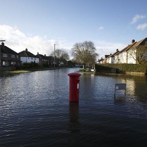 A postbox stands in a flooded street in Egham, Surrey