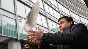 Jonathan Ganesh, president of the Docklands Victims Association, releases a dove during the 25th anniversary memorial service (Aaron Chown/PA)