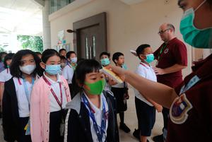 School officials check the temperatures of students before they enter a school in Tangerang, Indonesia
