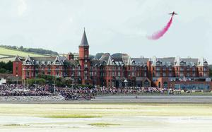One of the Red Arrows soars above the Slieve Donard Hotel in Newcastle as crowds look on at the Festival of Flight on Saturday