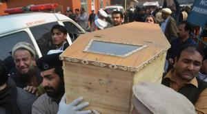 The coffin of one of the victims is carried yesterday in Peshawar