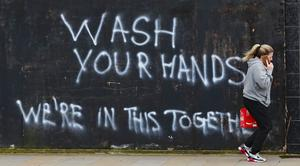 A woman walks past graffiti calling on people to wash their hands in East Belfast (Niall Carson/PA)