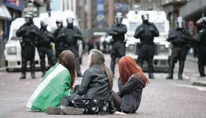 Police watch on as young people walk and sit through the city centre