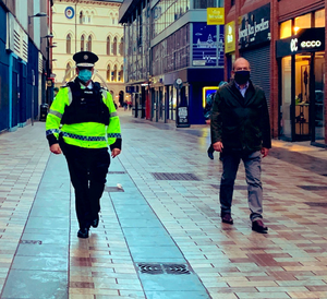 Patrol: PSNI Chief Constable Simon Byrne (left) with chief medical officer Dr Michael McBride in Belfast city centre