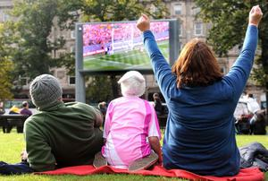 A family watching rugby on the big screen