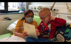 A member of the hospital staff helps Blake with his letter