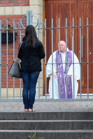 Fr Paddy McCafferty hearing confessions while observing social distancing