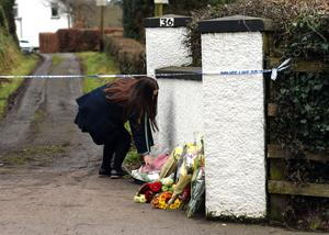 A woman leaves flowers at the scene