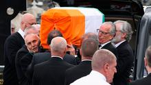 Gerry Kelly and Gerry Adams help carry the coffin