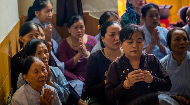 Family members of Pham Tra My attend a prayer ceremony with Buddhist monks in Vietnam
