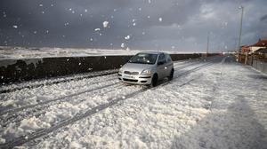 A car is driven through the foam whipped up by the sea near Blackpool
