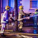 Firefighters douse the building with water