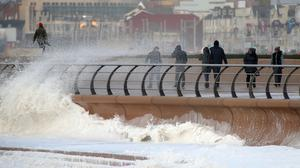 People on the promenade in Blackpool, as the stormy weather is causing disruption across parts of the UK with power cuts, ferry and train cancellations and difficult driving conditions.
