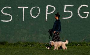 A woman walks her dog past anti-5G graffiti