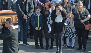 Joanne McGibbon is surrounded by her four children as her husband Michael's remains are brought into Holy Cross Church in north Belfast