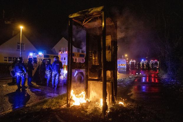 A phone box was set alight and surrounding roads were blocked with fires (Liam McBurney/PA)