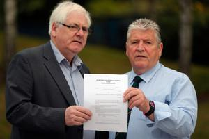 Michael Gallagher (left) who lost his son, Aiden, and Stanley McComb (right), who lost wife Ann in the Omagh bombing, hold a writ in the Omagh Memorial Garden