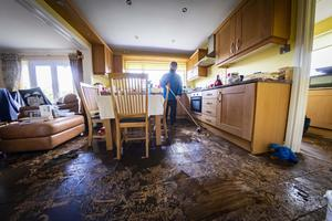 Harry Sage attempts to clean his home after floodwaters caused him to flee