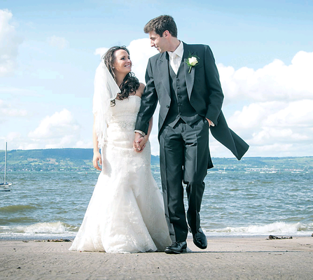 Alistair Cardy and his beautiful bride Sarah Hamilton walk hand-in-hand along Runkerry beach where the hockey-mad groom first proposed