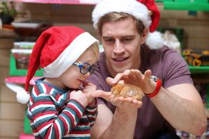 Ulster Rugby star Andrew Trimble with two-year-old Micah Campbell and one of a clutch of chicks from the charity's Unwrapped range of alternative Christmas gifts