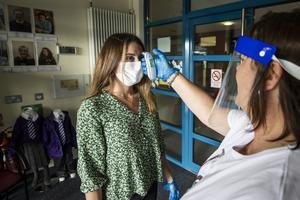 Teacher Catherine McClean has her temperature checked by assistant teacher Hilary Brennan at St Clare's Primary School in Belfast wearing PPE, as primary 7 year pupils are allowed to return to school in Northern Ireland. PA Photo. Picture date: Monday July 03, 2020. See PA story ULSTER Coronavirus. Photo credit should read: Liam McBurney/PA Wire