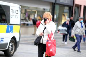 Covering up: Shoppers wearing masks in Belfast city centre today