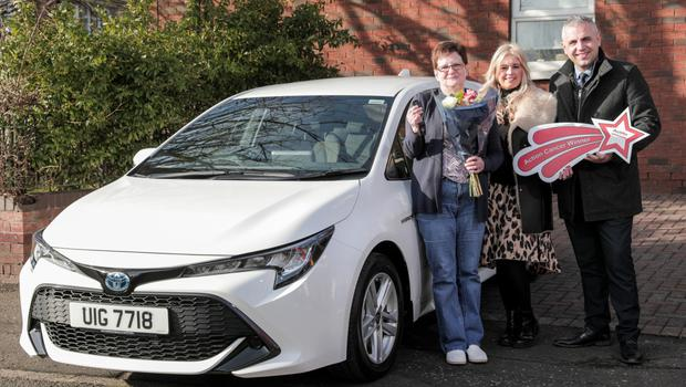 Liz Borland with her new car and representatives from Action Cancer and Charles Hurst