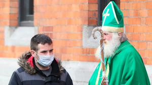 Portent: A man wearing a face mask walks past a man dressed as St Patrick last March
